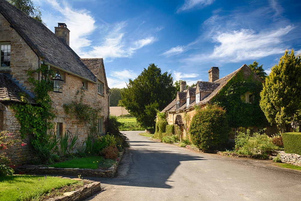 Ancient cotswold stone houses and flower garden in Cotswolds village of Icomb